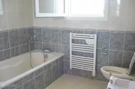 De badkamer is helemaal betegeld en heeeft een bad, een toilet en een meubel met 2 wastafels.