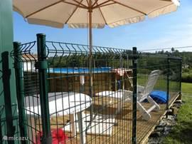 heeft een terras met afgesloten hekken voor de veiligheid van kinderen. Het terras ligt gedeeltelijk achter het zwembad.
