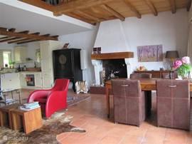 Zicht vanaf het terras naar de woonkamer, eethoek met open haard en de keuken