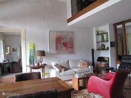 De comfortabele zithoek in de woonkamer met zicht op het terras aan het meer. Voorzien van dubbele openslaande deuren. Schuifdeur naar de woon/slaapkamer op de begane grond