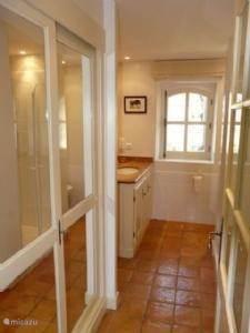 Badkamer op de begane grond met kasten met schuifdeuren aan twee kanten van de badkamer en doucheruimte tegenover de wastafel