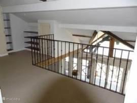 Zicht op de woonkamer vanaf de vide op de  eerste verdieping