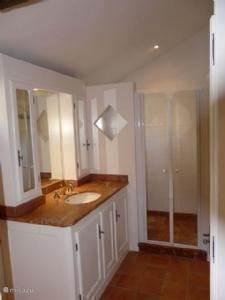 Badkamer op de eerste verdieping met doucheruimte en kasten boven wastafel en kasten daar tegenover