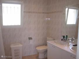 The bathroom has a bath,shower,  toilet, and 2 washbasins.