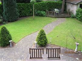 Vanaf balkon uitzicht op de tuin met enkele zitjes.