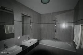 De badkamer met dubbele wastafel en een tweepersoonsbad.  De 2e badkamer heeft een dubbele douche.