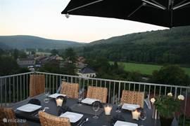 Balkon met ruime eetgelegenheid voor 8 personen en prachtig uitzicht over het dorpje en de rivier!
