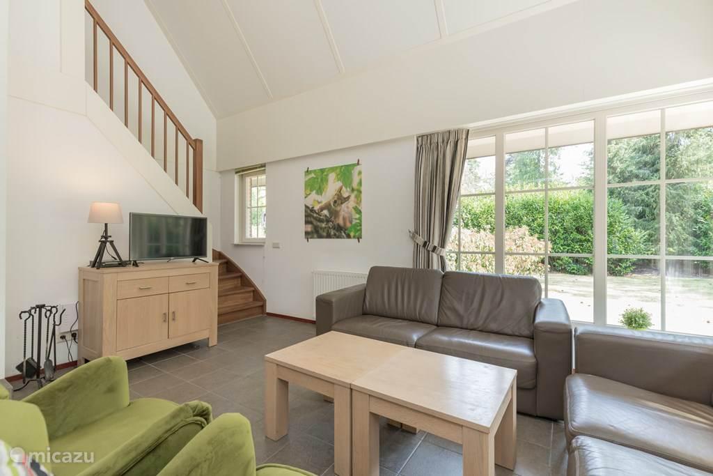 Modern ingerichte ruime woonkamer met mooie leren banken en stoelen.