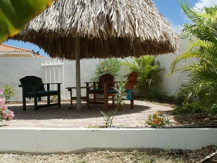 Het intieme achtertuin terras, met zitje en een ronde palapa. De slaapkamer 1 komt met een deur uit op dit intieme terras.