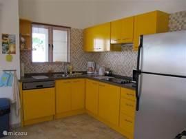 De complete keuken in de vrolijke troupial kleur. En de grote koelkast met vriezer.