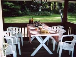 Twee overdekte terrassen met eettafel. Hier de grootst gedekt voor het avond eten.
