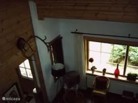 Een blik vanuit de vide in de ruime kamer waarin 2 banken, 2 fauteuils, 2 stoelen, salontafel, werktafel, tv (sateliet) radio)