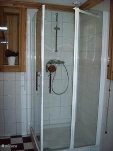 sfeervolle badkamer met ligbad, douche en wastafel.