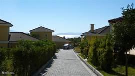 Het parkje met de tien huizen is goed onderhouden. Aan het eind van de met groen omzoomde weg door het park, treft u uw vakantiehuis aan. Op de foto is dat achter de auto. Vooraan gelegen, dus geen andere villa's op het park die uw uitzicht blokkeren.