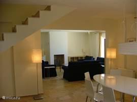De huiskamer en eetkamer liggen in elkaars verlengde. De vloeren zijn van prachtig hardsteen.