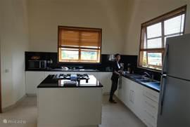 Keuken met kookeiland.Op de foto Ilu onze hulp.