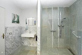 The marble, comfortable brand new bathroom which is equipped with large shower, toilet and sink. For the disabled are brackets on the wall and is a wheelchair shower present.