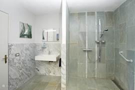 De marmeren, splinternieuwe comfortabele badkamer welke voorzien is van ruime inloopdouche, toilet en wastafel. Voor minder-validen zijn beugels aan de wand bevestigd en is een douche-rolstoel aanwezig.