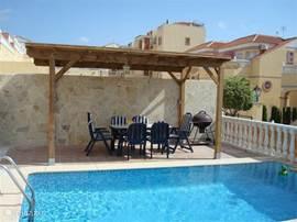 Achter het huis bevindt zich het zwembad met rondom terras. Aan één zijde staat onder een vaste overkapping met verlichting een tafel met zes stoelen.