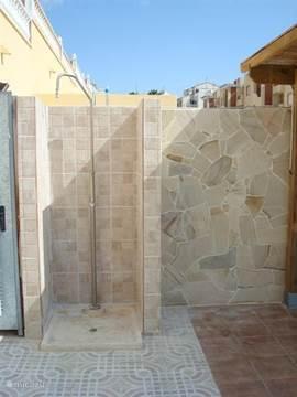 De buiten douche bevindt zich direct achter de woning bij de keukendeur.