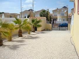Tuin aan de zijkant van de woning. Hier kan naast het schuurtje de auto op eigen terrein geparkeerd worden.