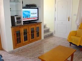 In de woonkamer de TV/audiohoek. Flatscreen TV met Nederlandse zenders, radio, CD/DVD speler en Wifi aansluiting.