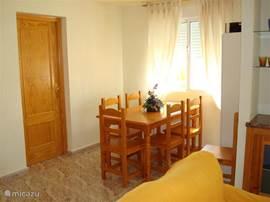 Eethoek met grote eettafel en zes stoelen. Achter de deur ligt de derde slaapkamer.