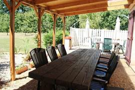 Covered south facing terrace with wooden table and reclining armchairs.