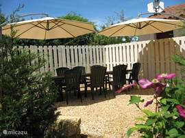 Open south-facing terrace with wooden table, reclining armchairs, large parasols and BBQ