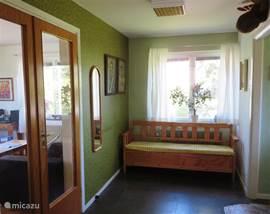 De centraal gelegen hall. Aan de linker kant de woonkamer en aan de rechter kant de WC en de voordeur. Achter de fotograaf, de keuken.