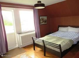Slaapkamer 1 , met een 2-persoons bed. Vanaf het balkonnetje heeft u een prachtig uitzicht over het weiland en het dorp Sorby.