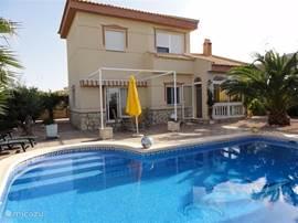 Voor aangezicht van het huis, zonneterras en zwembad.