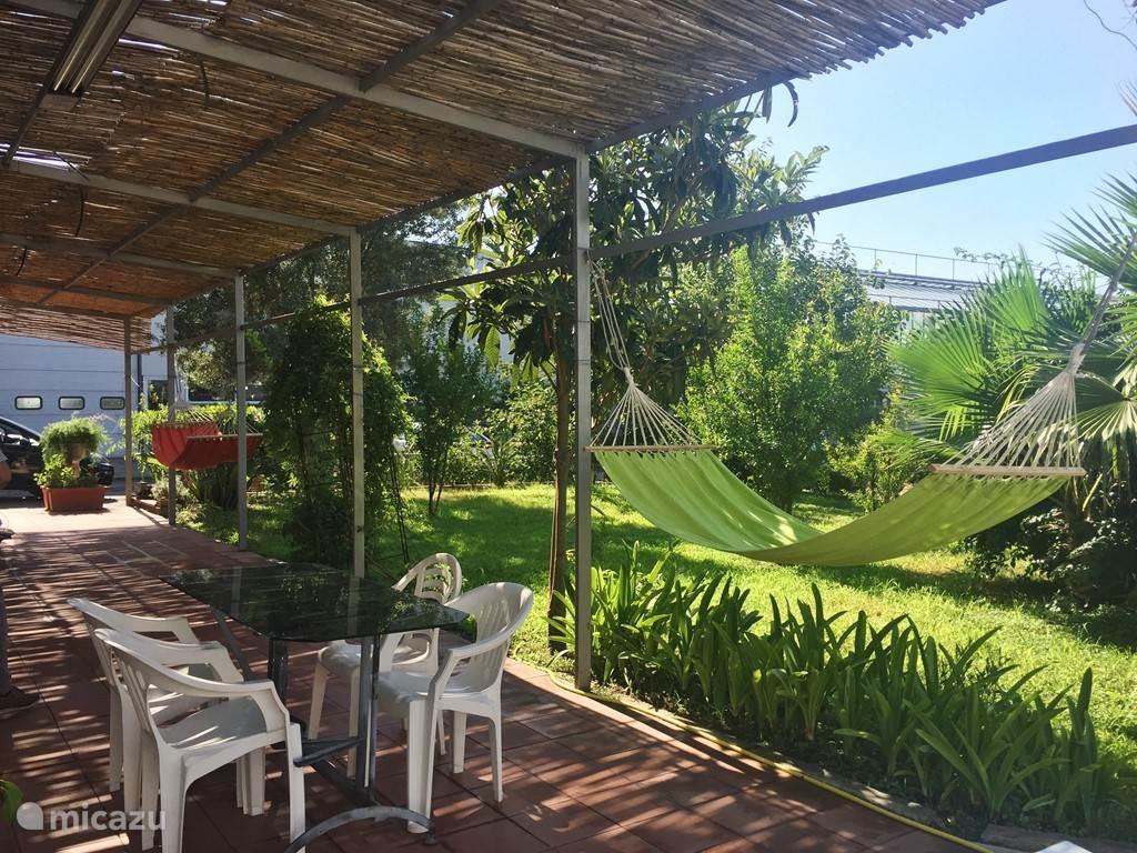 Appartement 2: terras met tuin, hangmatten en eetgedeelte