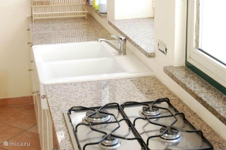 Appartement 2: Keuken met dubbele wastafel, fornuis, oven en grote koelkast