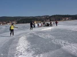 Koek en zopie op het bevroren meer. U ziet het Riviera Lipno park op de achtergrond. Ook genieten van deze unieke gebeurtenis? Ga naar de kalender en boek!