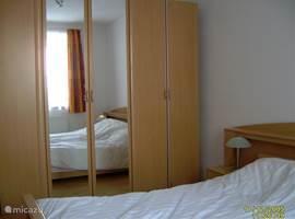 Ruime slaapkamer met grote kast, 2 nachtkastjes en leeslampjes. Het draai/kiepraam is voorzien van een vliegenhor.