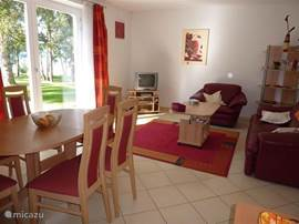 Gezellige woonkamer met openslaande deuren naar terras en uitzicht op het Lipno meer.