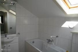 Badkamer boven met ligbad en wastafelmeubel.