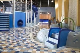 Indoor waterspeeltuin met waterspeeltplaats voor de kleintjes, glijbaan en welnessdeel (inclusief en bubbelbad sauna).