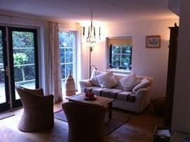 De gezellig zitkamer die aan de achterzijde van het huisje ligt met uitzicht op de tuin.