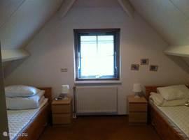 Deze slaapkamer is aan de achterzijde gelegen met twee éénpersoonsbedden met onderschuifbedden.