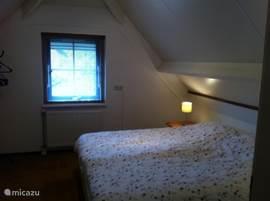 Deze slaapkamer ligt aan de voorzijde en heeft een twee-persoonsbed met twee separate matrassen.