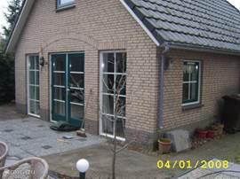 De achterkant van het huis met dubbele openslaande deuren.