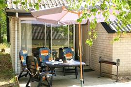 Terras met tuinset, parasol, barbeque.
