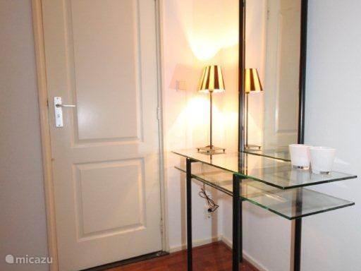 Entree met toegangsdeur naar  de badkamer en rechts naast de spiegel is de toegang tot de woonkamer