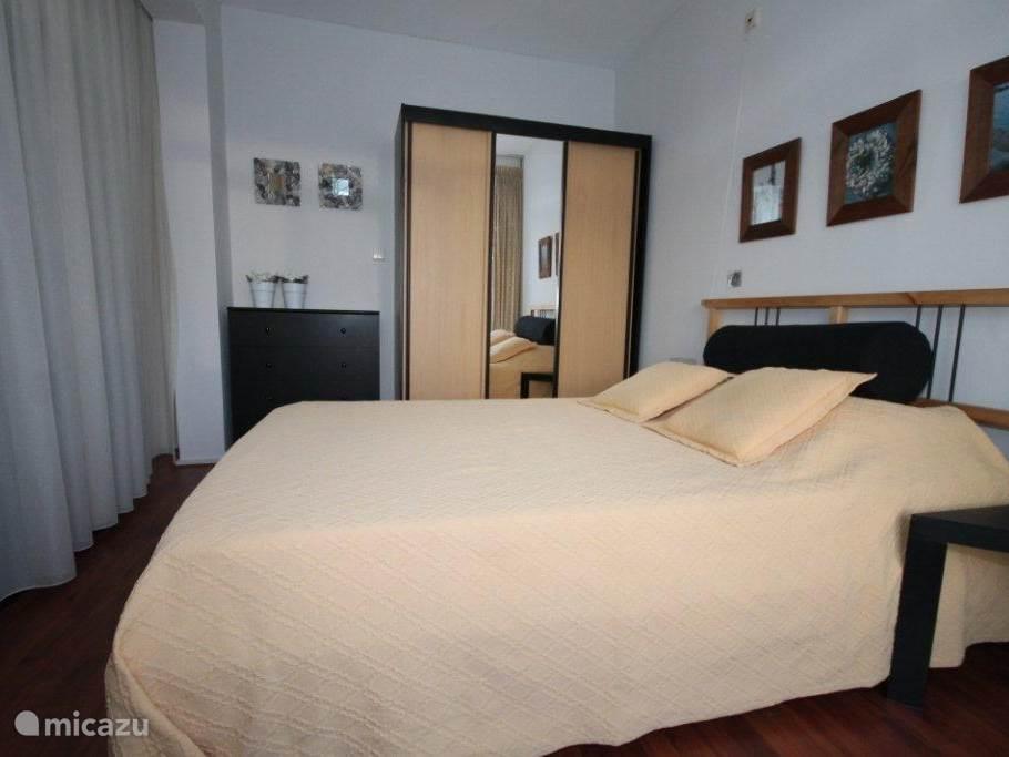 Slaapkamer met AUPINGSPIRAAL en TOPDEKMATRAS .  Aangrenzend het balkon.