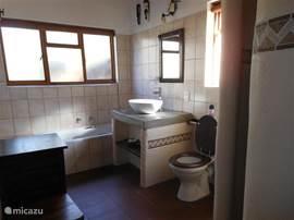 één van de badkamers met inloopdouche (regendouche), wastafel, ligbad en toilet