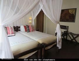één van de ruime slaapkamers met openslaande deuren naar een terras met zitgroep en buitendouche