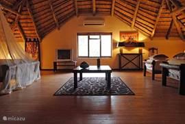 de grote loft met 4 bedden met muskietennetten, TV/DVD-speler, zitgroep en kledingkast