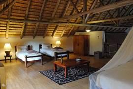 de grote loft met 4 bedden met muskietennetten, TV/DVD-speler, zitgroep en kledingkast.